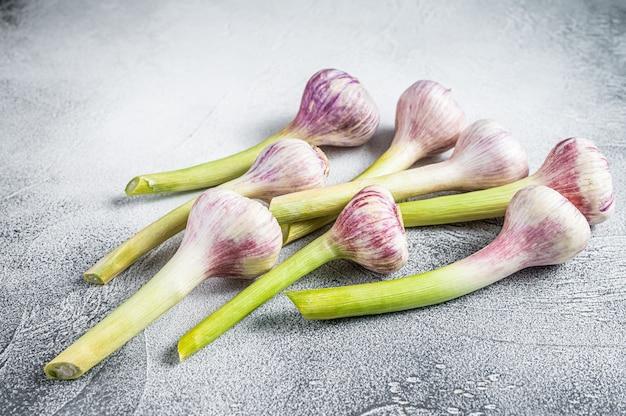 Весенние молодые луковицы чеснока на кухонном столе. белый фон. вид сверху.