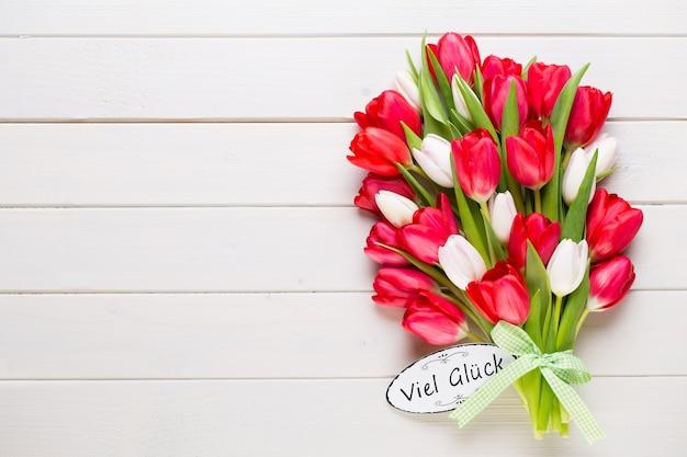 Время спрингта. букет красных тюльпанов на белом фоне деревянных.