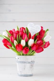 春の時間。白い木製の背景に赤いチューリップの花束。