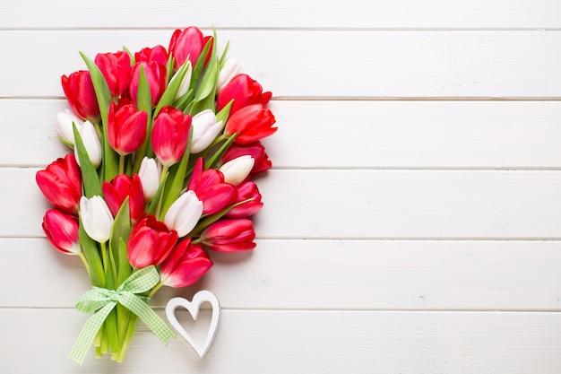 Время спрингта. букет красных тюльпанов на белой деревянной поверхности.
