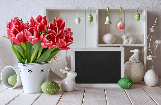 Springtime background with easter decorations and a chalk board, text space
