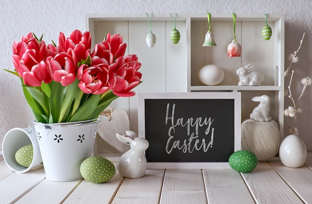 Springtime background with easter decorations and a chalk board, text