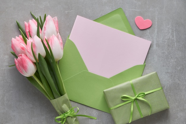 Springtime blue  background with pink tulips, wrapped gift box and decorative hearts