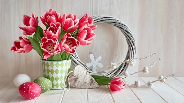 Весеннее украшение розовыми полосатыми тюльпанами, пасхальными яйцами, деревянным сердечком и плетеным венком на светлом дереве