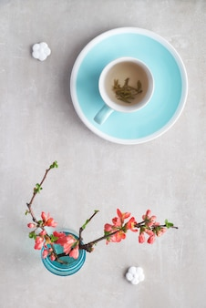 Springtime flat lay cup of green tea and japanese quince flowers on a grey stone, copyspace-
