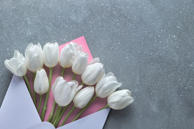Springtime flat lay, white tulips in white and pink envelope