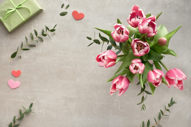 Springtime flat lay with bunch of pink tulips, eucalyptus leaves and gift boxes on stone