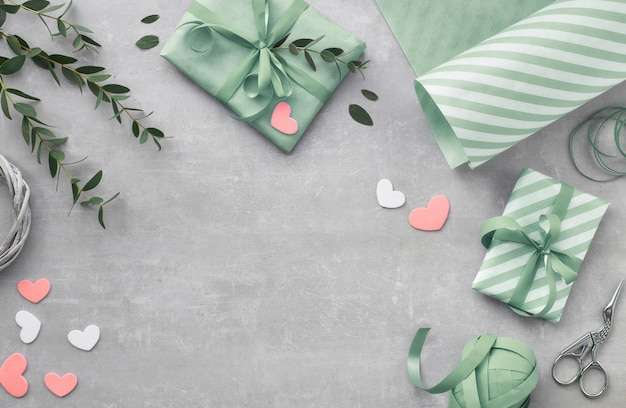 Springtime flat lay with gift boxes, hearts and eucalyptus leaves