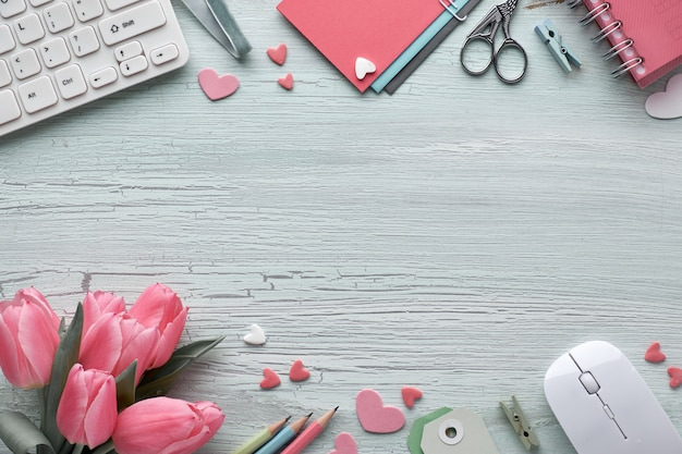 Springtime flat lay with keyboard, mouse, pink tulips, stationary, greeting cards, decorative hearts and copy-space