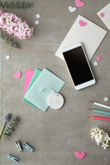 Springtime flat lay with pearl hyacinth flowers, eucalyptus, mobile phone and gift postcards