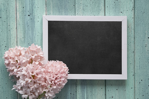 Springtime flat lay with pink hyacinth flowers and blackboard with text