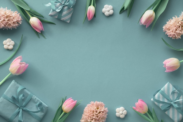 Springtime green and blue  wall with pink tulips, hyacinth and spring decorations, copy-space