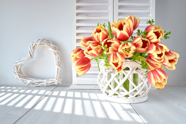 Springtime greeting card design with bunch of red tulips and spring decorations on light wood