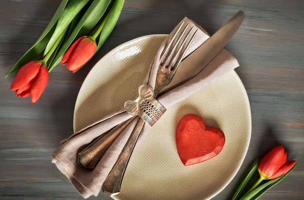 Springtime menu concept with fresh tulips and heart decoration on gray wood