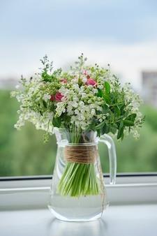 春、スズランの春の新鮮な花束、ピンクのバラ、咲くガマズミ属の木