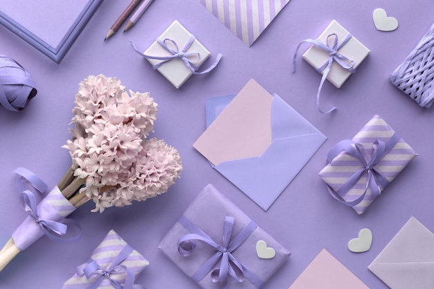 Springtime violet  background with pink tulips, hyacinth, wrapped gift boxes and small hearts