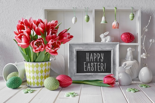 Springtime  with easter decorations and a chalk board. display cabinet with different objects and pink tulips