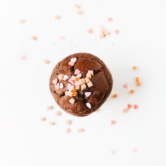 Sprinkle and caramel candies on chocolate cupcake isolated on white background