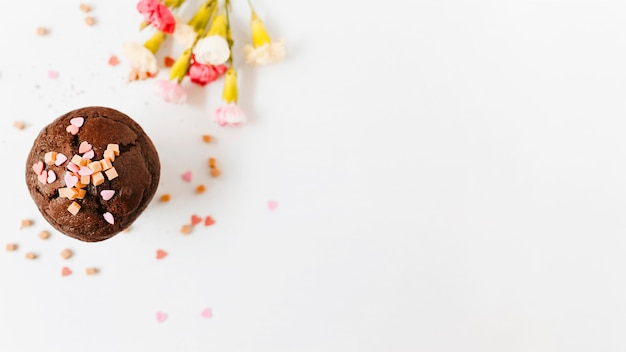 Sprinkle and caramel candies on chocolate cupcake with flower on white background