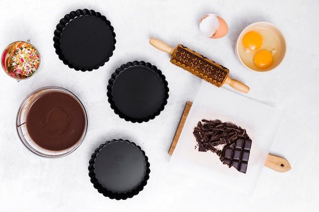 Sprinkle; egg yolk; rolling pin; chocolate bar; syrup and three empty cake holder on white background