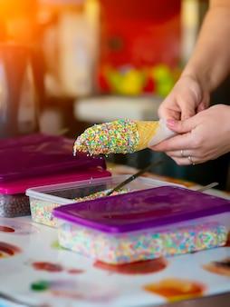 Посыпать мороженое в вафельном стаканчике с глазурью