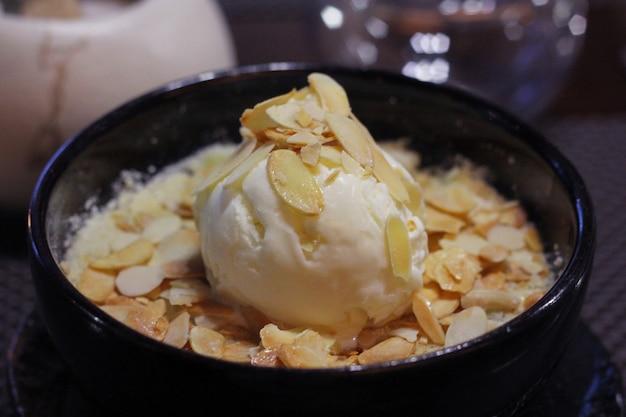 Посыпать яблочную крошку ванильным мороженым. десерт в кафе.