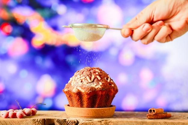크리스마스 컵케이크에 가루 설탕을 뿌린다. 크리스마스를 위한 달콤함을 배경으로
