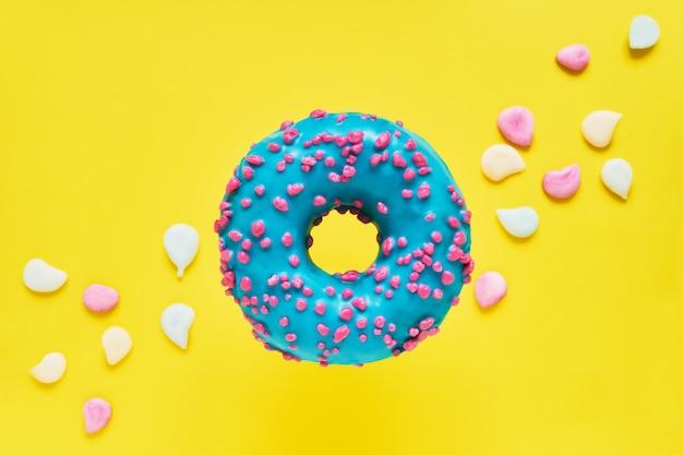 Посыпать синим пончиком. глазированный пончик на желтый