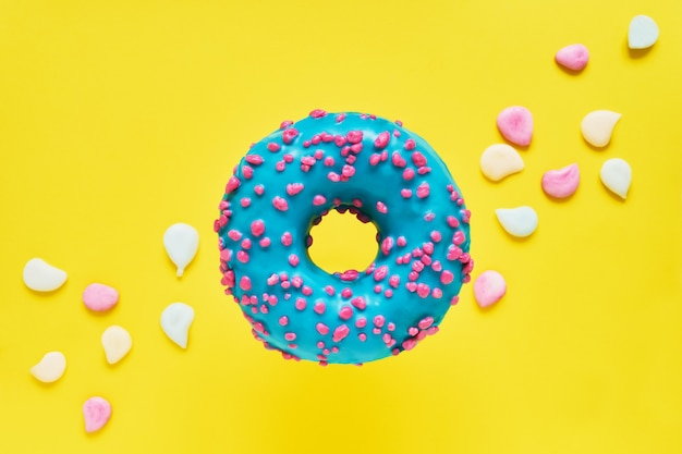 Sprinkled blue donut. glazed sprinkled donut on yellow