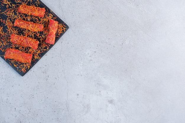 Рахат-лукум на доске, на мраморном фоне, посыпанная ледяной глазурью.