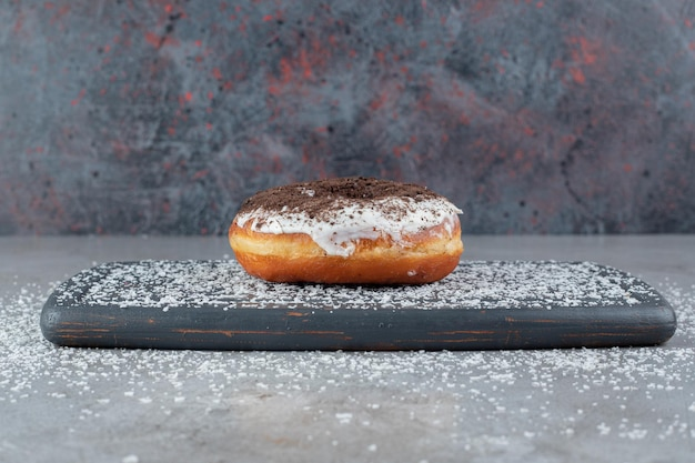 Sprinkled coconut powder around a donut on a tray on marble surface