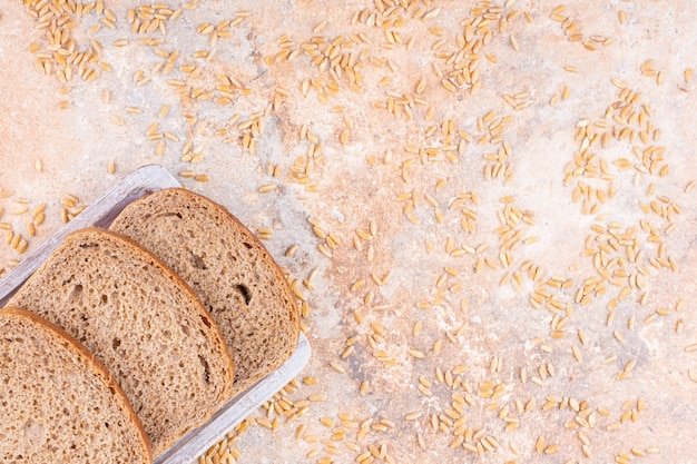 Sprinkled grain next to sliced bread on a wooden plate, on the marble background.