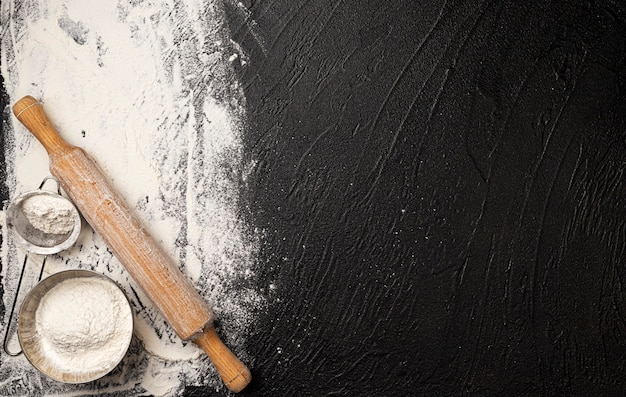 Sprinkled wheat flour and wooden rolling pin on black background, cooking banner with copy space for text