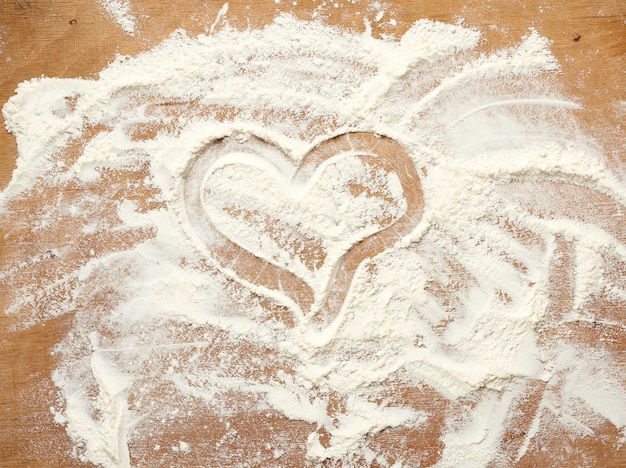 Sprinkled white wheat flour on a brown wooden background