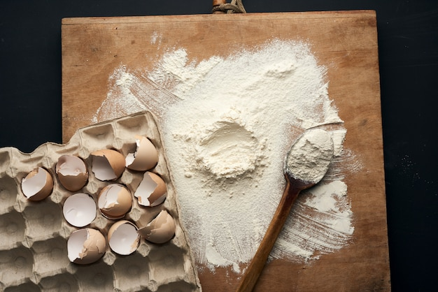 ペーパートレイに白い小麦粉、木製の麺棒、丸いふるい、鶏の卵殻を振りかけた