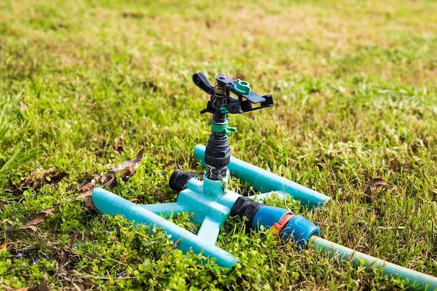 緑の芝生に散水するスプリンクラーヘッド。
