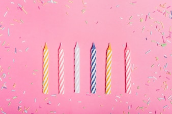 Sprinkles and row of candles on pink backdrop