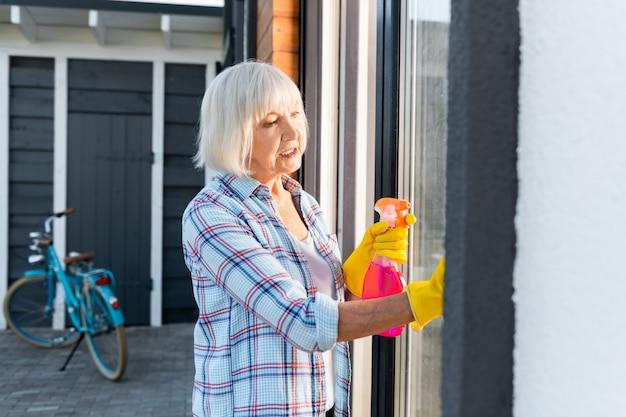 水をまきます。夏の家の外の窓を洗っている間水をまき散らすブロンドの髪の引退した女性