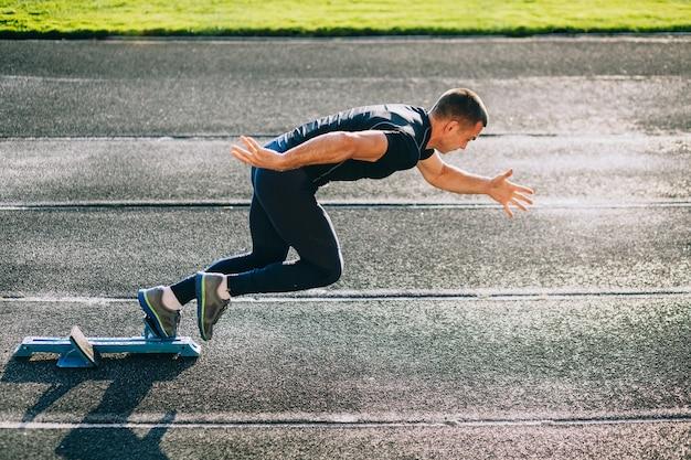 Sprinter leaving starting blocks on the running track