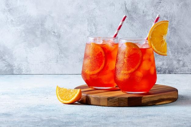 水色の背景の上の木の板に氷とオレンジのスライスとグラスのスプリッツカクテル。