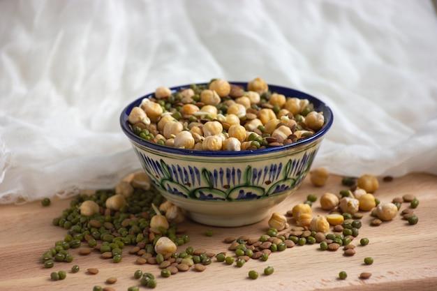 木製と白のテキスタイルのカラフルなボウルに発芽ひよこ豆、レンズ豆、緑豆