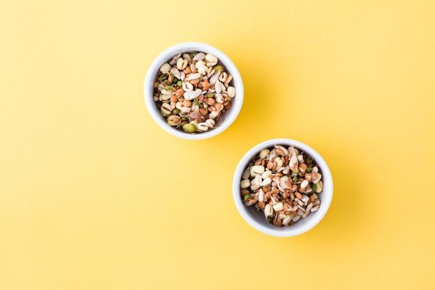 녹두, 렌즈 콩, 아마, 해바라기의 알갱이가 노란색 테이블에 그릇에 담겨 있습니다. 평면도. 공간 복사