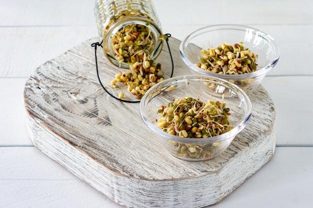 白いテーブルの上のボウルにもやしを発芽させた。健康的なコンセプト、マクロビオティック食品。