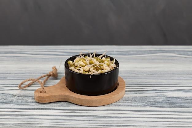 검은 그릇에 녹두를 발아. 건강한 채식 음식.