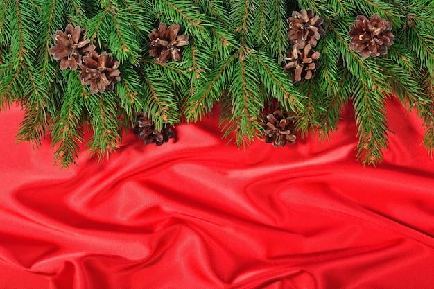 トウヒの枝と赤い背景の上の円錐形のクローズアップ