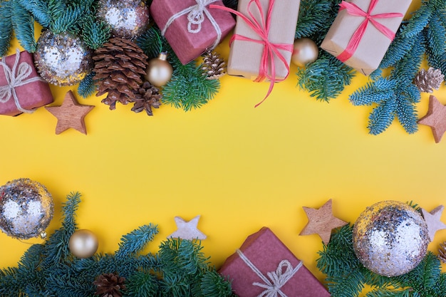 Spruce branch, cones and vintage toys decoration on christmas or new year on yellow background
