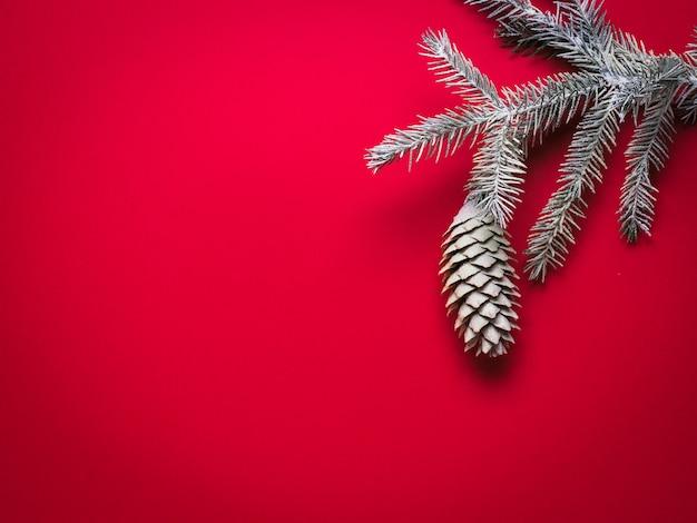 赤い背景の雪の中で大きな円錐形のトウヒの枝