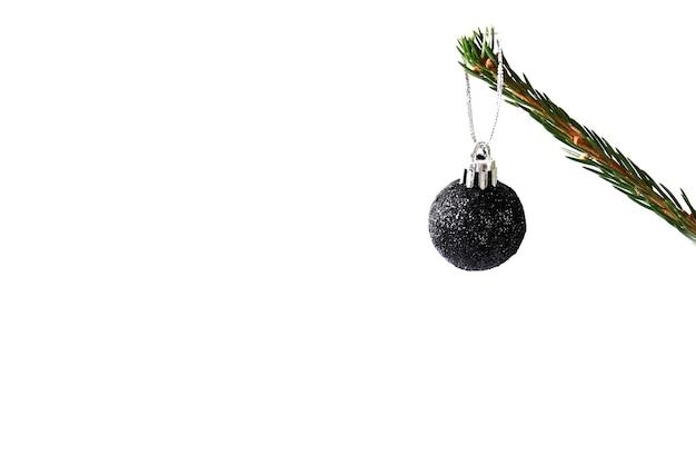 白い背景の上の黒いクリスマスボールとトウヒの枝。クリエイティブなミニマルなクリスマスコンサート