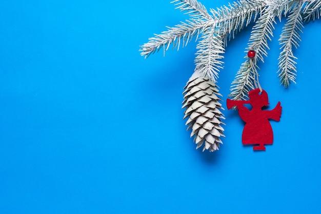 雪の中に円錐形のトウヒの枝と天使の形の装飾。クリスマスの準備