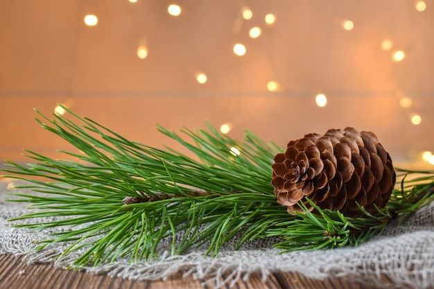 Spruce branch with a big cone on the background of christmas lights. christmas bokeh. happy new year and christmas.